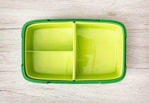 Green plastic box for food storage on the wooden background